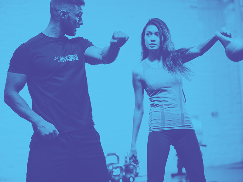 Personal trainer showing a gym member how to use a kettle bell
