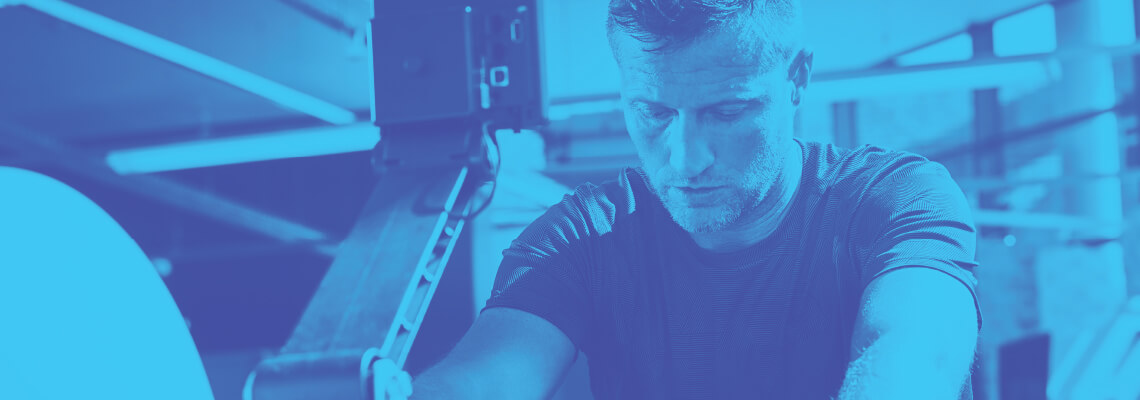 Man looking down as he works out on fitness equipment