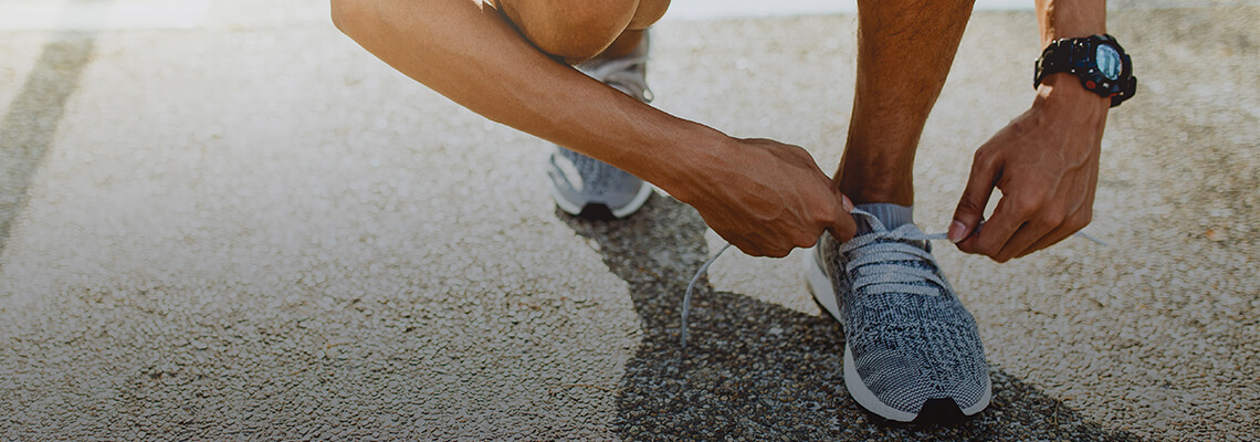 Person tying the shoe lace on a pair of runners