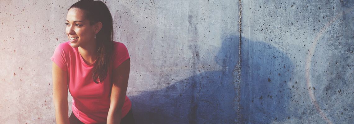 Woman sat against a grey wall smiling
