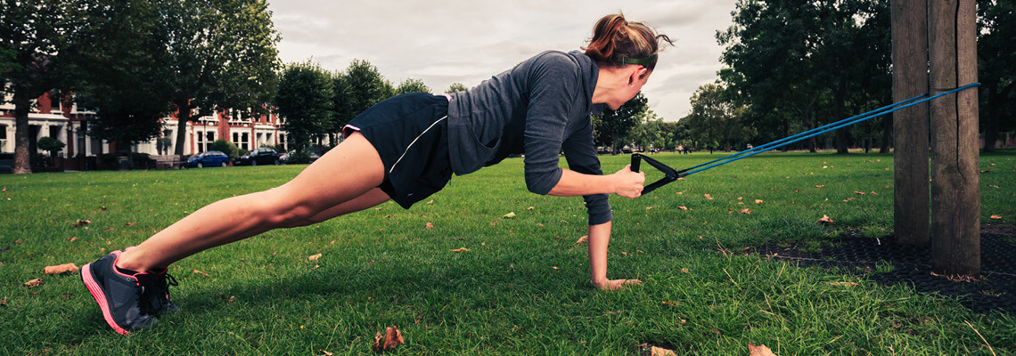 Woman working out outside with a resistance band around a tree