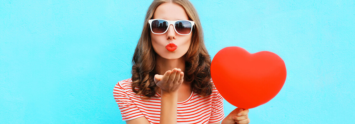 Woman holding a red heart blowing a kiss