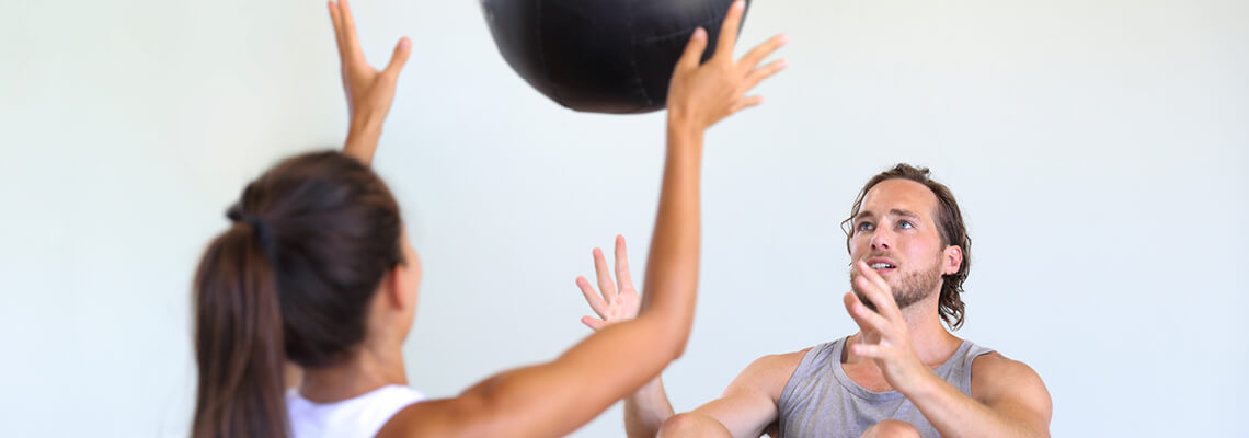 Man and woman throwing an exercise ball between them