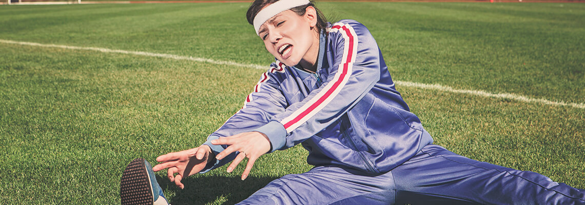 Woman in a tracksuit trying to stretch and touch her toes