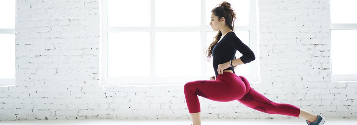 A woman doing a lunge wearing workout clothing