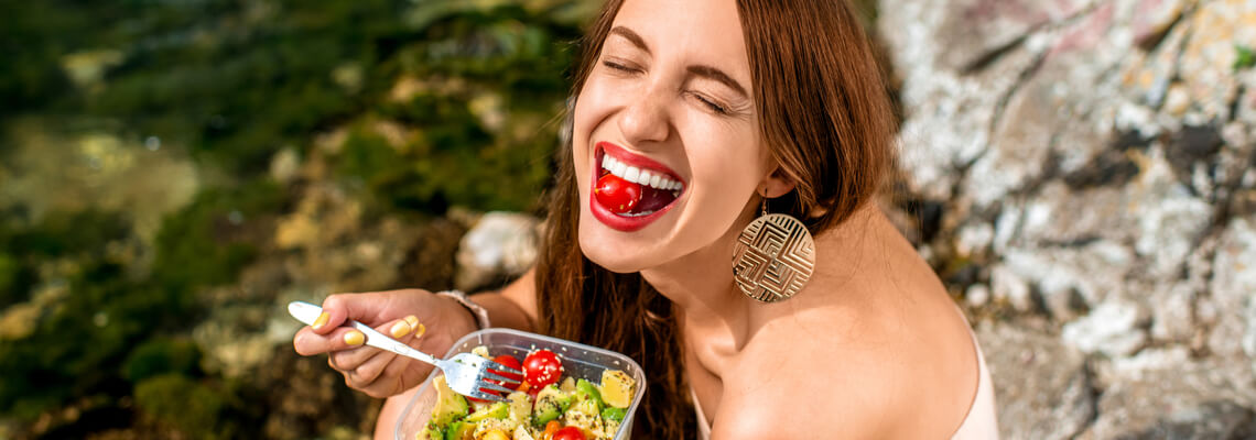 Woman eating salad smiling with a tomato in her mouth