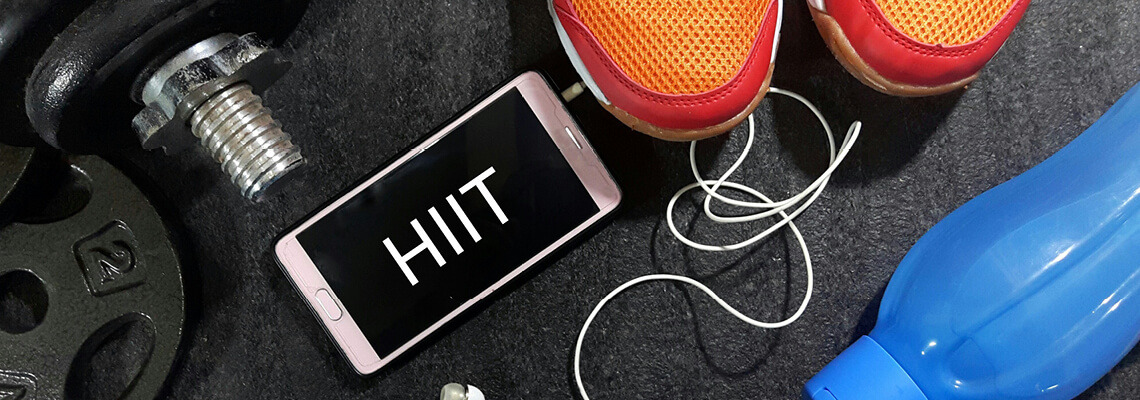 A mobile phone screen displaying the word HIIT surrounded by gym equipment