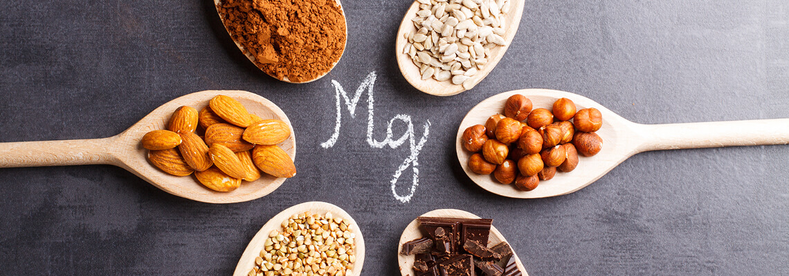 Wooden spoons with various nuts, chocolate and spices around the letter Mg