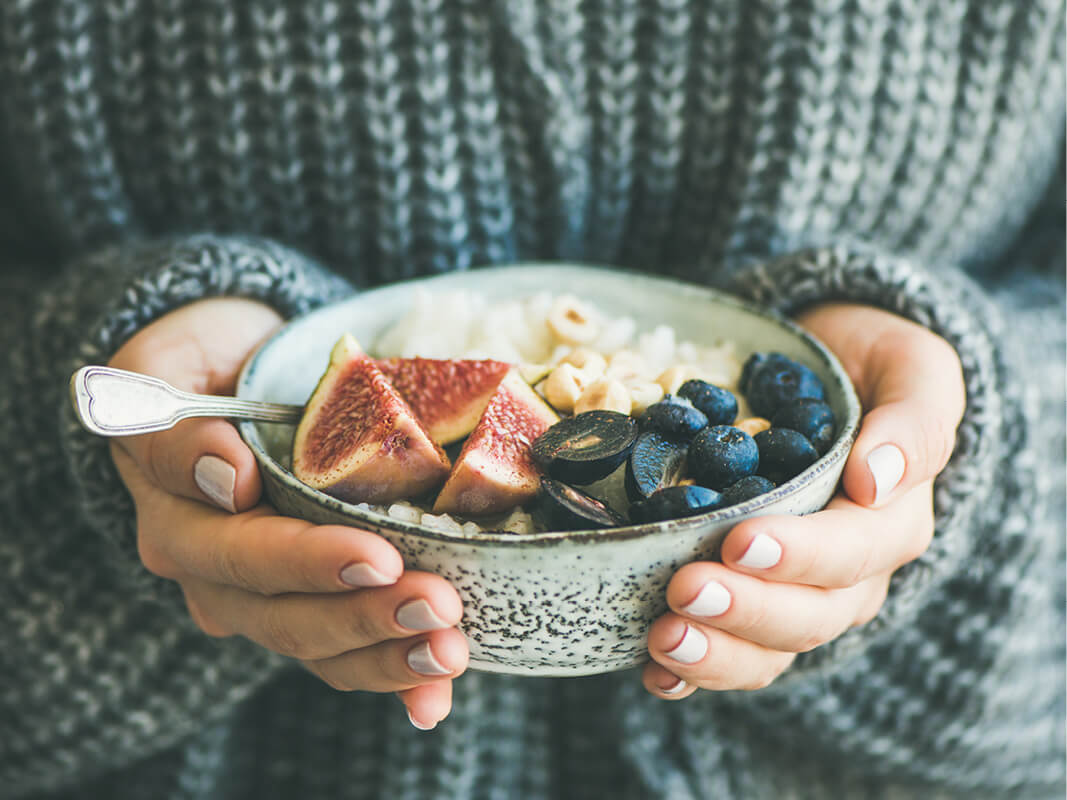 Hands holding a bowl of fruit and grains